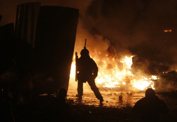 A man is silhouetted against burning tyres set ablaze by pro-European protesters during clashes with riot police in Kiev