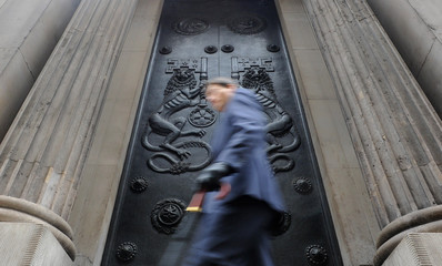 A man passes a doorway at the Bank of England in the City of London