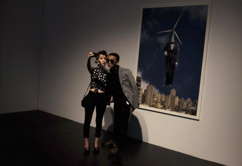 """Visitors take a """"selfie"""" with a mobile phone during Sao Paulo Fashion Week"""