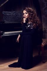 Beautiful thoughtful girl sitting near piano. Fashion studio portrait