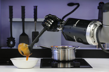 A robot in the Robotic Kitchen prototype created by Moley Robotics cooks a crab soup at the company's booth at the world's largest industrial technology fair, the Hannover Messe, in Hanover