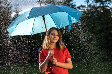 Happy girl under an umbrella in the rain