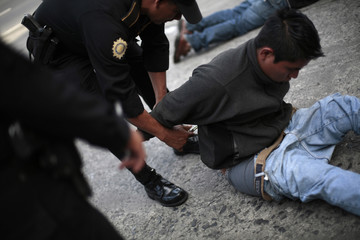 A police officer detains a man for participating in a robbery with an accomplice in Guatemala City