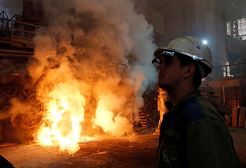 A worker observes an electric arc furnace in a steel factory of Store Steel in Store
