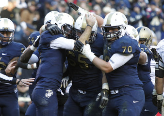 Navy corner back Lonnie Richardson (L) celebrates his first half touchdown against Army with teammates Josh Cabral (65) and Graham Vickers in their football game in Landover, Maryland