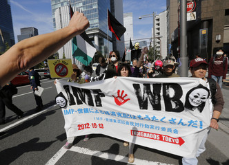 Protesters march with a placard after a rally against the annual meetings of the IMF and the World Bank Group in Tokyo