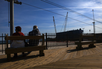 People sit at a boardwalk that was damaged by hurricane Sandy in October 2012 in Seaside Heights, New Jersey
