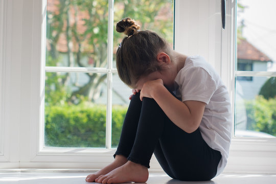 Sad little girl sitting on the window sill hiding her eyes, selective focus