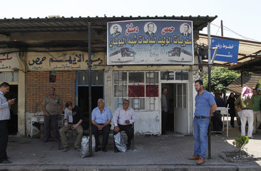 People wait for buses at the al-Abassin bus station, near Damascus' Jobar neighbourhood