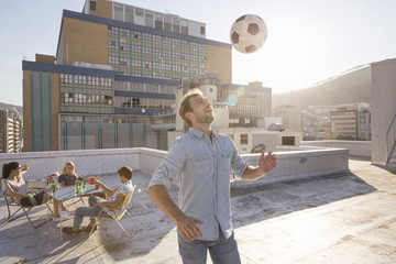 Friends meeting on rooftop terrace in summer, playing football