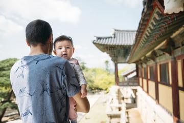 South Korea, Gyeongju, man traveling with a baby girl in Bulguksa Temple