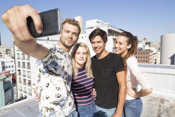 Friends taking selfies on a rooftop terrace