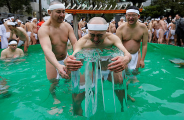 Men wearing loin cloths hold on to ice as they bathe in ice-cold water outside the Teppozu Inari shrine in Tokyo