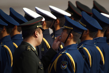 An officer touches underneath the nose of a member of an honour guard as he inspects them at Beijing airport
