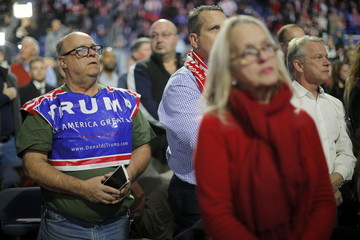Audience members stand during the playing of the U.S. national anthem at a campaign rally with  Trump in Lowell