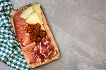 Spanish cold cuts (embutidos). Cheese, sausage and ham on gray table