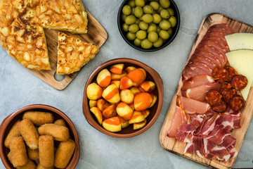 Traditional spanish tapas. Croquettes, olives, omelette, ham and patatas bravas on gray stone