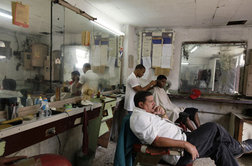 A worker waits for customers as another cuts hair at a barber shop in Havana