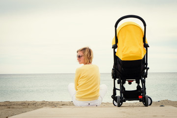 Young mother relaxing on beach with baby stroller outdoor. Back view