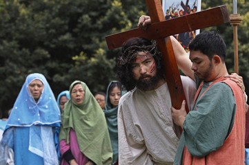 An actor portraying Jesus Christ and an actor portraying Simon take part in a re-enactment of the stations of the cross in Taipei