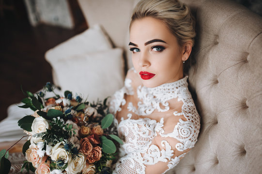 Beautiful bride in a lace dress with an original wedding bouquet in a vintage interior. Studio.