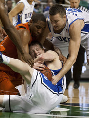 Duke Blue Devils Singler fights for a loose ball against Virginia Tech Hokies Davila  at the 2011 ACC Tournament in Greensboro, North Carolina