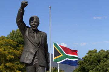 The South African flag flies at half mast behind the iconic Mandela statue at the entrance of the Groot Drakenstein Prison
