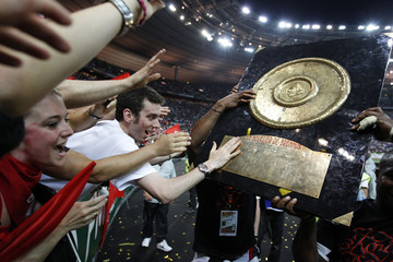 """Stade Toulousain fans touch the """"Bouclier de Brenus"""" trophy after their win against Montpellier Herault in their French rugby union final match at the Stade de France in Saint-Denis"""