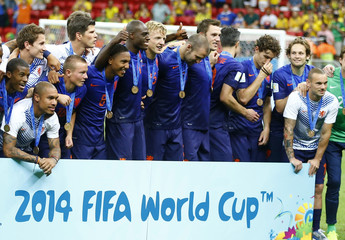 The Netherlands team poses for pictures after winning their 2014 World Cup third-place playoff against Brazil at the Brasilia national stadium in Brasilia