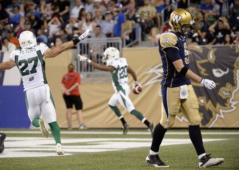 Blue Bombers quarterback Willy walks off the field after giving up a touchdown interception to Roughriders' Maze during CFL game in Winnipeg