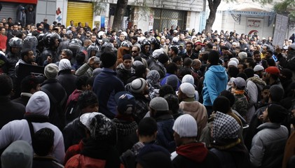 Protesters stand in front of riot police during a demonstration in Tunis