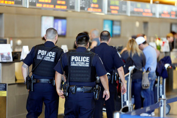 Officers with the U.S. Customs and Border Protection walk past ticket counters during the travel ban at Los Angeles International Airport (LAX) in Los Angeles, California