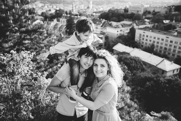 Black and white portrait happy family of three. Father hugging mother and holding his son on the back. They standing and smiling on the hill with city view.