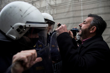 A health worker confronts with riot police during a demonstration against government plans affecting the health sector, near the Prime Minister's office in Athens