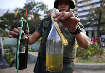 A National Guard shows bottles of molotov cocktails seized at Altamira square in Caracas
