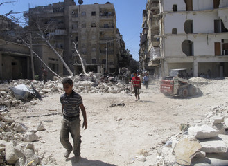 Men walk on rubble of buildings damaged by what activists said was shelling by forces loyal to President al-Assad in Aleppo