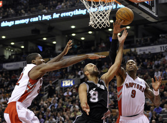 Spurs' Parker puts up a shot between Raptors' defenders Davis and Butler during their NBA basketball game in Toronto