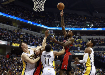Toronto Raptors center Johnson shoots the ball over Indiana Pacers forwards Hansbrough and George and guard Johnson during the first quarter of their NBA basketball game in Indianapolis, Indiana
