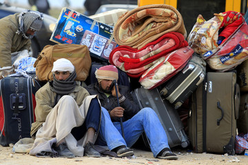 Egyptians sit next to their belongings as they wait for transportation near the Libyan and Tunisian border crossing of Ras Jdir after fleeing unrest in Libya