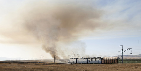 A freight train moves along the steppe, with smoke from burnt grass seen in the background, in Khakassia region