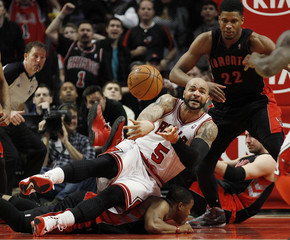 Chicago Bulls' Boozer makes a pass from the ground as Toronto Raptors' Gay looks on during the second half of their NBA basketball game in Chicago, Illinois
