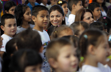 Costa Rica's President Laura Chinchilla is seen next to children as she attends the celebration of National Children's Day in Fatima
