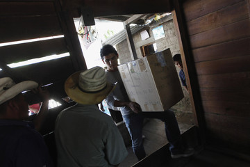 An anthropologist carries a box to containing the skeleton of Rojas, who disappeared during the internal armed conflict, in house of Rojas' son in Rabinal