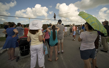 Fans watch as high wire walker Nik Wallenda balances on a 1,200 foot-long cable during a practice session in Sarasota, Florida