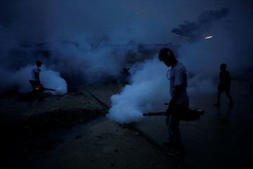 Workers of the Ministry of Public Health and Population fumigate in the street against mosquito breeding to prevent diseases such as malaria, dengue and Zika, during a fumigation campaign in Port-au-Prince, Haiti