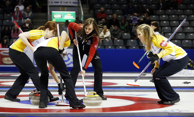 Ontario's Homan sweeps a shot against Manitoba's Askin and Lawes as Jones looks on during the twelfth draw at Scotties Tournament of Hearts curling championship in Kingston