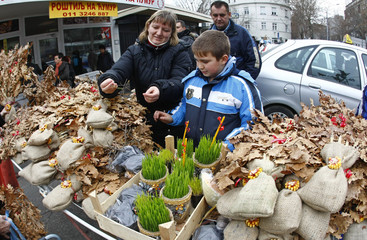 People buy dried oak leaf branches and wheat, symbols of the traditional Yule log in Belgrade