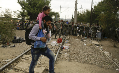 A migrant carries a child to board a train near Gevgelija