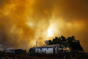 Smoke fills the air over a small barn turning the sky orange as the High Park Fire burns near Laporte, Colorado