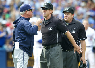 First base umpire Jeff Kellogg steps between Tampa Bay Rays manager Joe Maddon  arguing with home plate umpire Paul Schrieber in Toronto